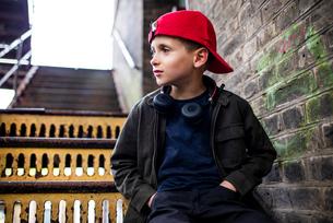 Boy sitting on metal staircaseの写真素材 [FYI03611765]