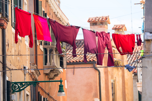 Red and pink clothing on clothesline outside traditional houses, Venice, Veneto, Italyの写真素材 [FYI03611825]