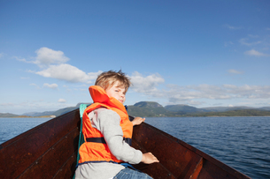 Boy looking back from front of rowing boat, Aure, More og Romsdal, Norwayの写真素材 [FYI03611867]