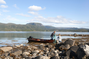 Mature man passing rope to son from rowing boat, Aure, More og Romsdal, Norwayの写真素材 [FYI03611868]