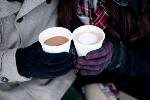Young couple in winter gloves holding takeaway drinks, close up of handsの写真素材 [FYI03611919]