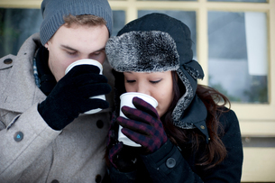 Young couple in winter hats drinking takeaway coffeeの写真素材 [FYI03611923]