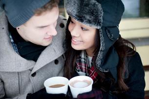 Young couple in winter hats having takeaway drinksの写真素材 [FYI03611924]
