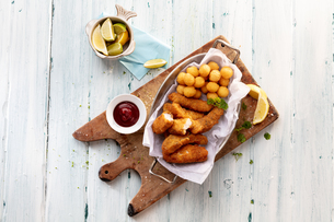 Cheese croquettes and potato balls on cutting board with tomato sauce , still life, overhead viewの写真素材 [FYI03611939]