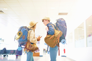 Young couple at airport, carrying backpacks, standing face to face, talkingの写真素材 [FYI03611946]