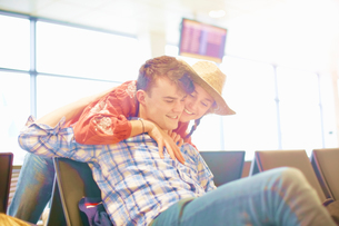 Young man sitting at airport, young woman reaching over seat to hug himの写真素材 [FYI03611948]