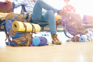 Young man sitting at airport, backpacks on floor beside him, low sectionの写真素材 [FYI03611950]