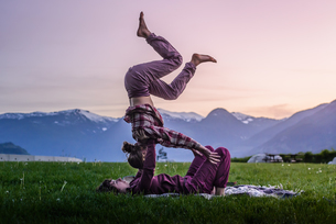 Two young women practicing acroyoga on grass in front of mountain range at sunset, Squamish, Britishの写真素材 [FYI03612068]