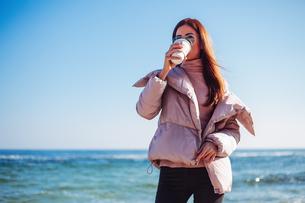 Stylish mid adult woman on beach drinking takeaway coffee, Odessa, Odeska Oblast, Ukraineの写真素材 [FYI03612102]