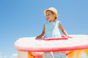 Girl in sun hat looking out from plastic roof on beach,  Castellammare del Golfo, Sicily, Italyの写真素材 [FYI03612151]