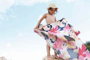 Girl standing on rock folding patterned blanket, Scopello, Sicily, Italyの写真素材 [FYI03612154]
