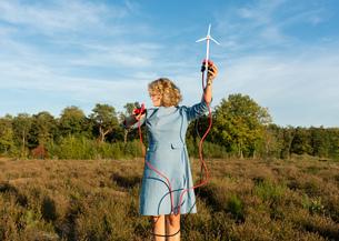 Teenage girl powering LED light using miniature wind turbine, Netherlandsの写真素材 [FYI03612203]