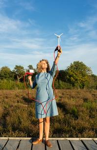 Teenage girl powering LED light using miniature wind turbine, Netherlandsの写真素材 [FYI03612204]