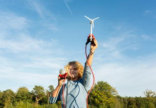 Teenage girl powering LED light using miniature wind turbine, Netherlandsの写真素材 [FYI03612206]