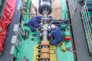 Overhead view of engineers inspecting gears on generator in turbine hall of nuclear power station duの写真素材 [FYI03612227]