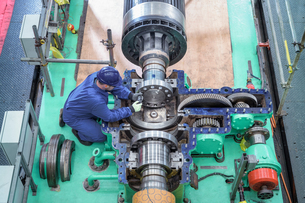 Overhead view of engineer inspecting gears on generator in turbine hall of nuclear power station durの写真素材 [FYI03612230]