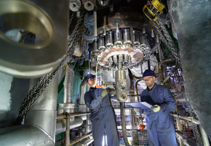 Engineers working in confined space under turbine during outage in nuclear power stationの写真素材 [FYI03612235]