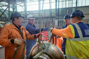 Engineers craning large gear into place in turbine hall of nuclear power stationの写真素材 [FYI03612246]
