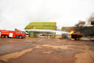 Firemen training, spraying water from fire engine at mock airplaneの写真素材 [FYI03612251]