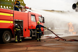 Firemen training, spraying water from fire engine at mock airplane engineの写真素材 [FYI03612252]