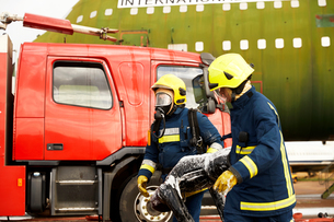 Firemen training, firemen in breathing apparatus carrying equipmentの写真素材 [FYI03612253]