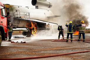 Firemen training, spraying water at mock airplane engineの写真素材 [FYI03612254]