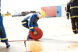 Firemen training, fireman unrolling fire hose at training facilityの写真素材 [FYI03612259]