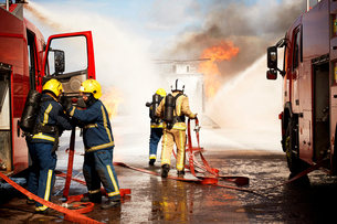 Firemen training, team of firemen extinguishing mock helicopter fire at training facilityの写真素材 [FYI03612276]