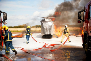 Firemen training, team of firemen extinguishing mock helicopter fire at training facilityの写真素材 [FYI03612277]