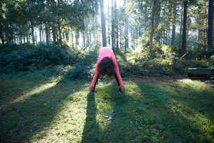 Young female bending forward stretching in forestの写真素材 [FYI03612300]