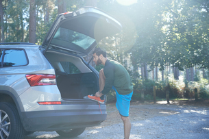 Male runner tying laces on car boot in sunlit forestの写真素材 [FYI03612317]