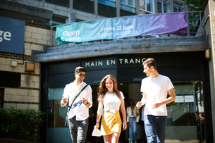 Teenage girl with young male higher education students leaving college campusの写真素材 [FYI03612340]