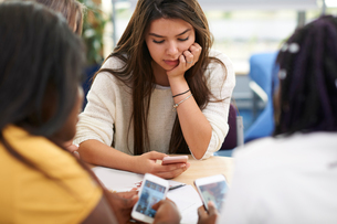 Female higher education students looking at smartphones in college classroomの写真素材 [FYI03612353]