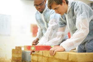Male higher education students building brick wall in college workshopの写真素材 [FYI03612370]