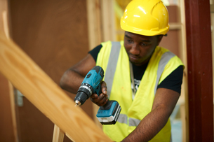 Male higher education student drilling wooden framework in college workshopの写真素材 [FYI03612372]