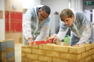 Male higher education students building brick wall in college workshopの写真素材 [FYI03612373]
