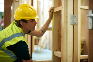 Male higher education student checking wooden framework in college workshopの写真素材 [FYI03612374]