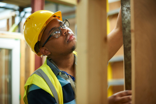 Male higher education student building wooden framework in college workshopの写真素材 [FYI03612376]