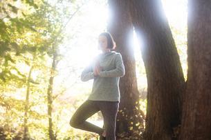 Cross country jogger practising yoga in parkの写真素材 [FYI03612573]
