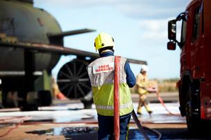 Fireman carrying fire hose over shoulder, Darlington, UKの写真素材 [FYI03612622]