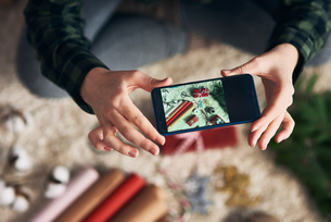 Woman taking photo of Christmas gifts and giftwrapの写真素材 [FYI03612628]
