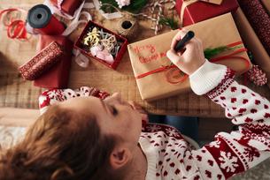 Woman writing greetings on Christmas presentsの写真素材 [FYI03612647]