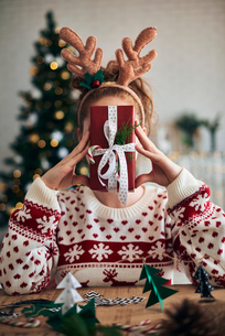 Woman behind Christmas present, Christmas tree shaped decorations in foregroundの写真素材 [FYI03612649]