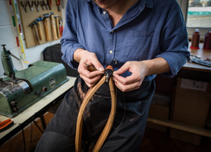 Leatherworker stitching leather in workshop, mid sectionの写真素材 [FYI03612748]