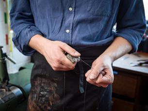 Leatherworker waxing thread in workshop, mid sectionの写真素材 [FYI03612749]