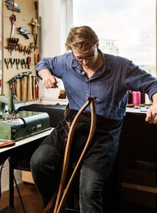 Leatherworker stitching leather handbag straps in workshopの写真素材 [FYI03612753]