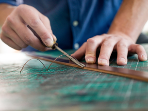 Leatherworker trimming leather for handbag strap in workshop, close up of handsの写真素材 [FYI03612754]