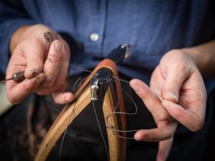 Leatherworker stitching handbag in workshop, close up of handsの写真素材 [FYI03612755]