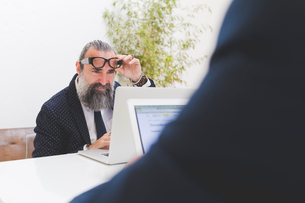 Businessman looking at laptop at office desk, over shoulder viewの写真素材 [FYI03612822]
