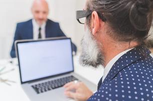 Businessman using laptop at office desk, over shoulder viewの写真素材 [FYI03612824]